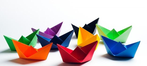 Helle farbige papierboote auf einem weißen hintergrund. speicherplatz kopieren Premium Fotos