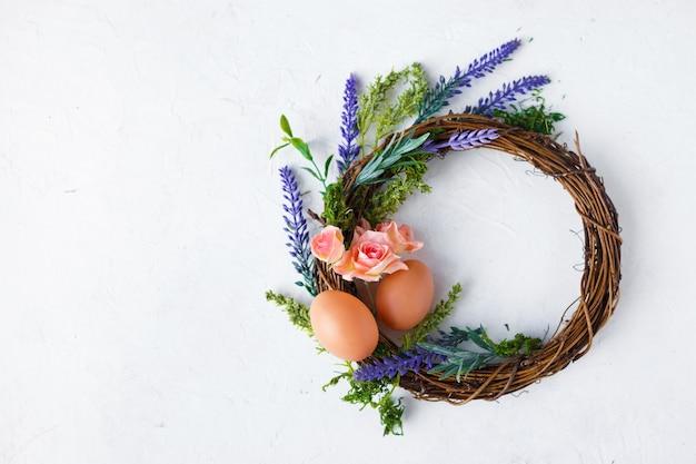 Helle frühlingsblumen, kranz mit ostereiern auf grau Premium Fotos