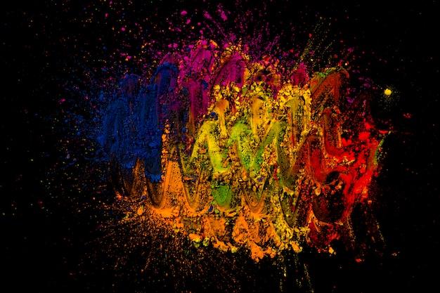 Helle holi farben gemischt mit dem finger über schwarzem hintergrund Kostenlose Fotos