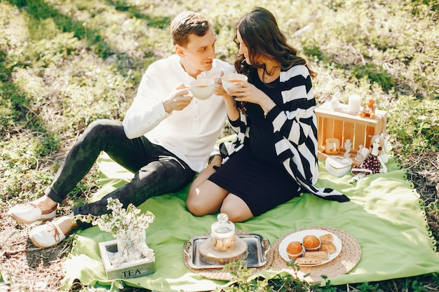 Helle und glückliche schwangere frau, die im park mit ihrem ehemann sitzt und einen tee trinkt Kostenlose Fotos