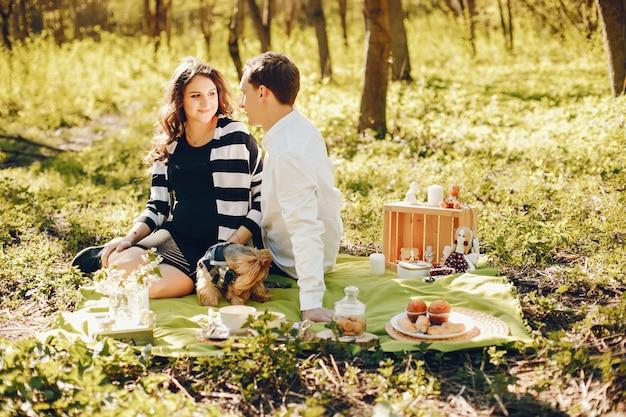Helle und glückliche schwangere frau, die im park mit ihrem ehemann sitzt Kostenlose Fotos