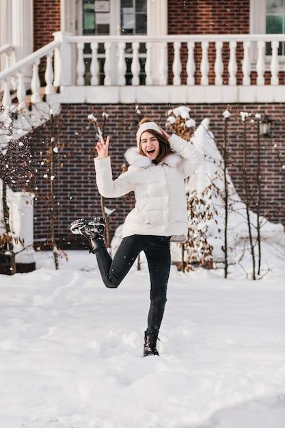 Helle wahre gefühle der aufgeregten stilvollen frau, die spaß im schnee auf der straße in der kalten winterzeit hat. lächeln, springen, strickmütze, warme kleidung, fröhliche stimmung, winterferien, gute laune. Kostenlose Fotos