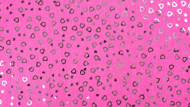 Heller rosa kreppapierhintergrund mit herzpailletten. Premium Fotos
