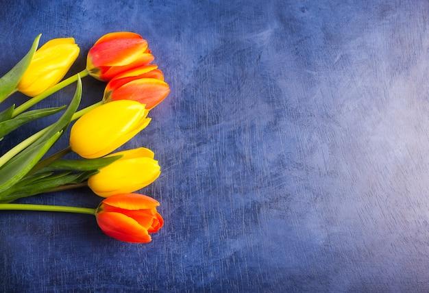 Heller tulpenblumenstrauß auf blauer tabelle Kostenlose Fotos