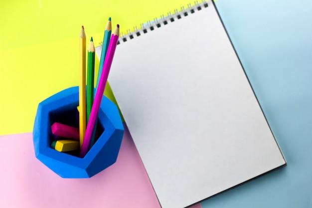 Helles arbeitsplatznotizbuch der draufsicht mit leerem blattkopieraum und hellen bleistiften Premium Fotos
