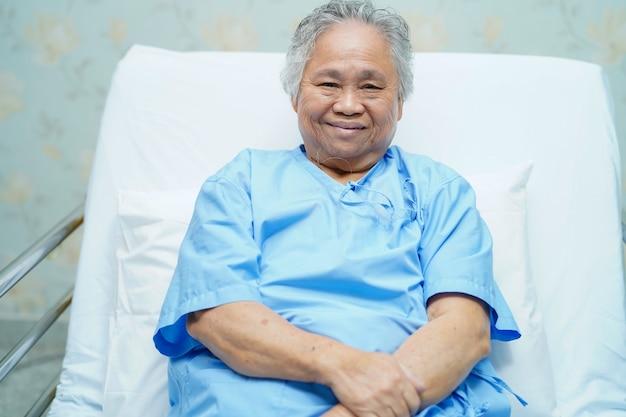 Helles gesicht des geduldigen lächelns der asiatischen älteren frau beim sitzen auf bett im krankenhaus. Premium Fotos