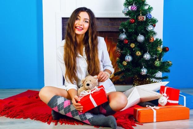 Helles porträt des innenlebensstils des glücklichen hübschen jungen mädchens, das zu hause ihren weihnachtsbaum sitzt Kostenlose Fotos
