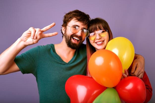 Helles positives porträt des glücklichen hübschen paares, das lächelt, friedensgeste zeigt und partyballons, familienbeziehung, violette wand hält Kostenlose Fotos