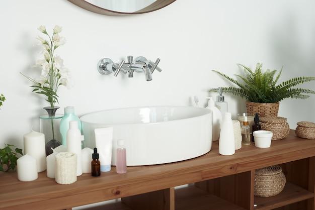 Helles waschbecken mit cremetuben, gläsern mit gesichtsseren und sauberen handtüchern. das konzept der hautpflege, des täglichen waschens und der sauberkeit. Premium Fotos