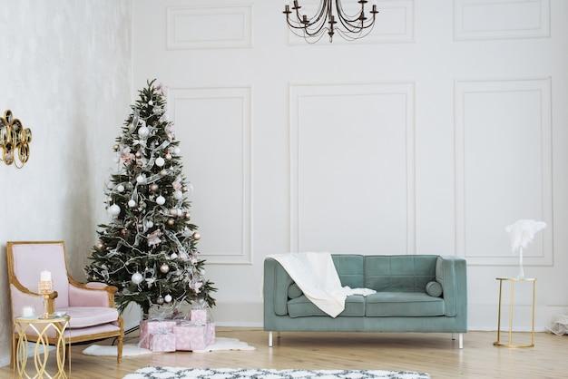 Helles weihnachtsinterieur. weihnachtsbaum mit geschenken darunter in beige- und rosatönen Premium Fotos