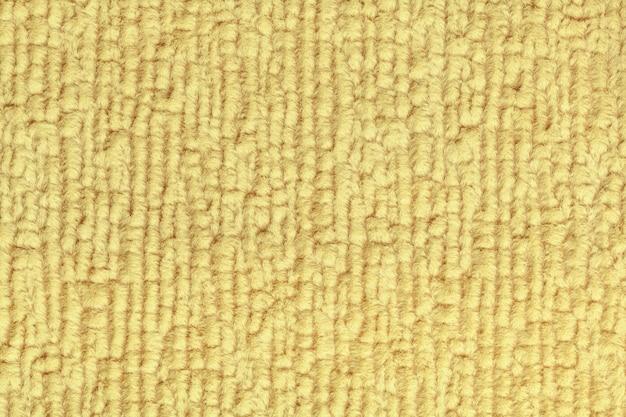 Hellgelber flauschiger hintergrund aus weichem, flauschigem stoff. beschaffenheit der textilnahaufnahme. Premium Fotos