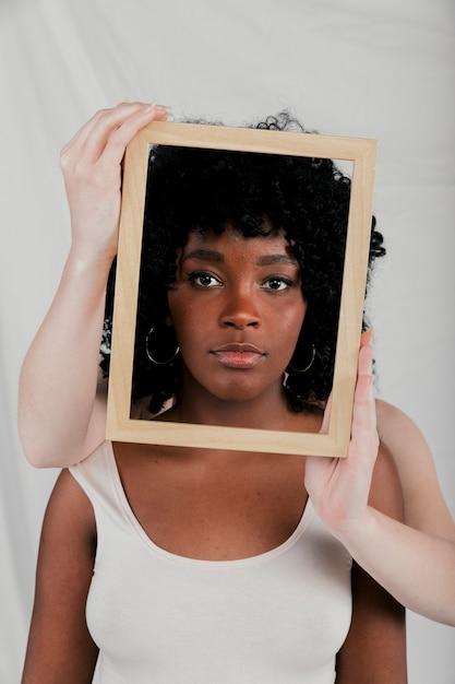 Hellhäutige hände der frau holzrandrahmen vor einer afrikanischen frau halten Kostenlose Fotos