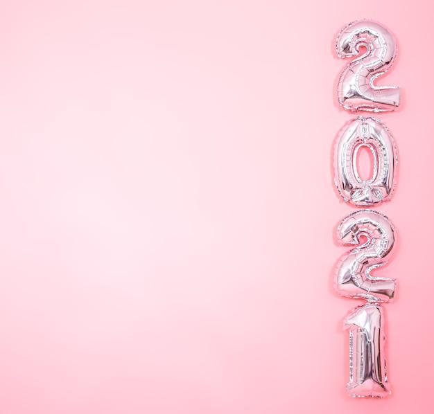 Hellrosa hintergrund mit silbernen neujahrsballons in form von zahlen auf der rechten seite, neujahrskonzept Kostenlose Fotos