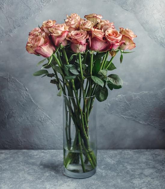 Hellrosa ombre-rosenstrauß in glasvase vor grauer wand Kostenlose Fotos