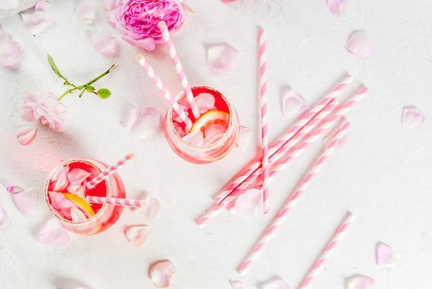 Hellrosa rosencocktail, mit roséwein, rosafarbenen blumenblättern des tees und zitrone auf einer weißen konkreten steintabelle. Premium Fotos