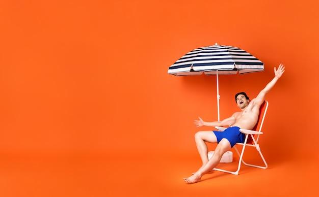Hemdloser glücklicher junger mann, der auf dem strandstuhl lächelt mit den ausgestreckten armen sitzt Premium Fotos