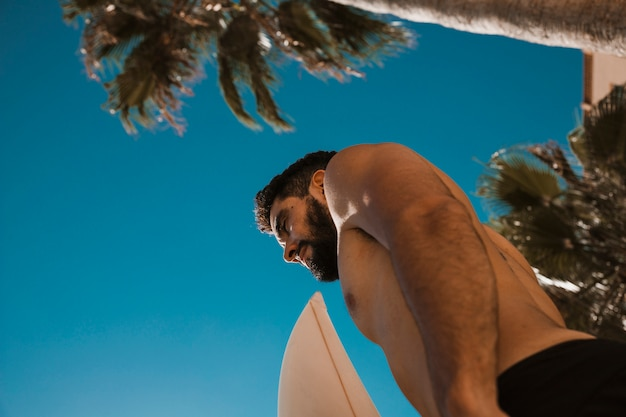 Hemdloser kerl mit surfbrett Kostenlose Fotos