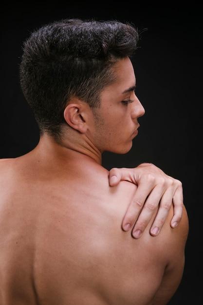 Hemdloser mann, der schultermuskeln ausdehnt Kostenlose Fotos