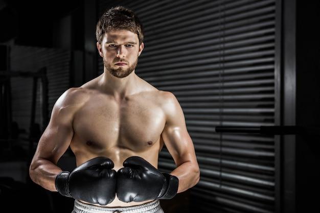 Hemdloser mann mit boxhandschuhen an der crossfit turnhalle Premium Fotos