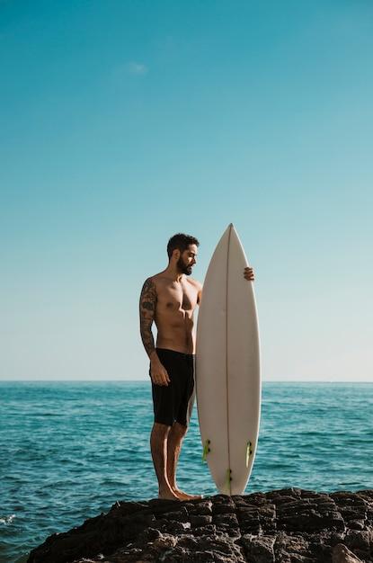 Hemdloser mann mit dem surfbrett, das auf felsen steht Kostenlose Fotos