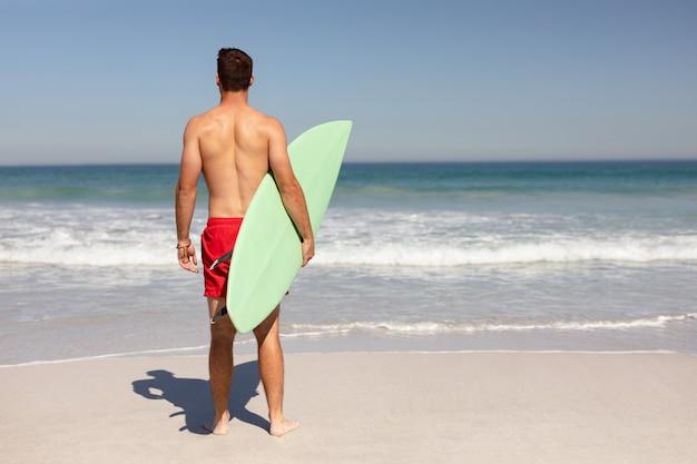 Hemdloser mann mit dem surfbrett, das auf strand im sonnenschein steht Kostenlose Fotos