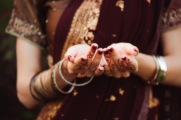 Henna hochzeit design, frau hände mit schwarzen mehndi tattoo. hände der indischen brautfrau mit schwarzen henna-tätowierungen. mode. indien Premium Fotos