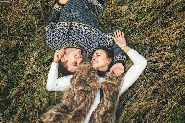 Herauf ansicht von den hübschen paaren, die im gras liegen. Premium Fotos