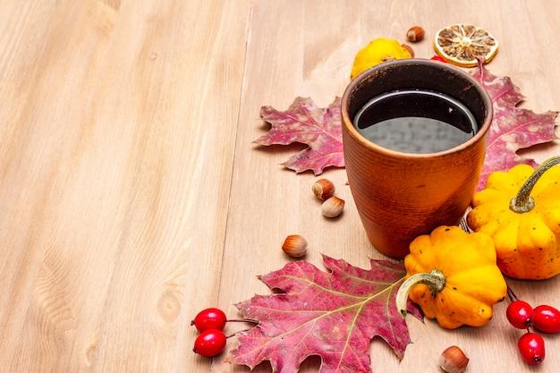 Herbst gemütliche stimmung zusammensetzung. heißer tee in keramikglas, herbstblätter, kürbisse, bruyere, haselnüsse Premium Fotos