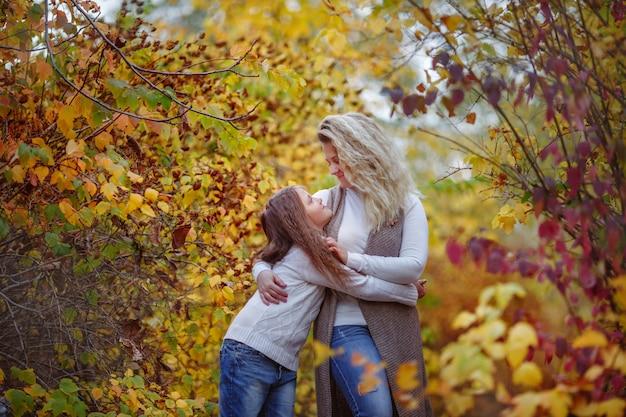 Herbst, mutter und tochter im herbst park Premium Fotos