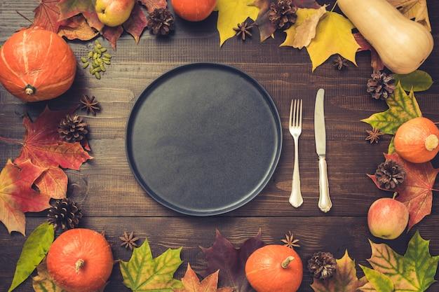 Herbst- und erntedankfestgedeck mit gefallenen blättern. Premium Fotos