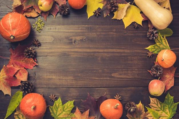Herbst- und erntedankfestgrenze von bunten blättern und von kürbis auf hölzernem brett. kopieren sie platz. fallen . goldener fall. Premium Fotos