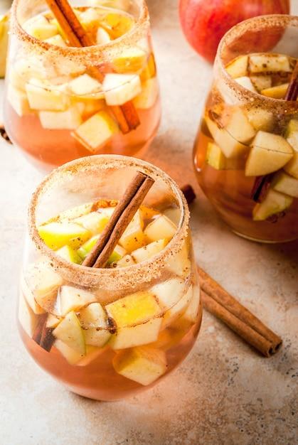 Herbst- und wintergetränke. warme apfelsangria, apfelwein mit fruchtstücken, zimt, gewürzen, zucker. in gläsern auf einem steinbeigen tisch. mit den zutaten. copyspace Premium Fotos