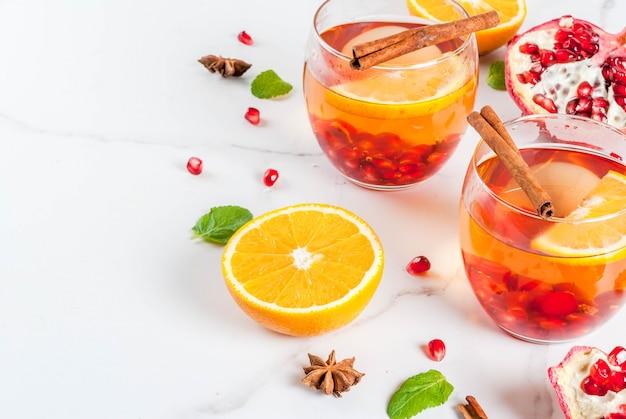 Herbst- und wintergetränke. warmes erfrischendes cocktail mit granatapfel, orangen, zimt, gewürzen und minze. auf einem weißen marmortisch. Premium Fotos