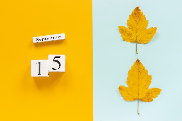 Herbst zusammensetzung. hölzerner kalender am 15. september und gelber herbstlaub auf gelbem blauem hintergrund. Premium Fotos