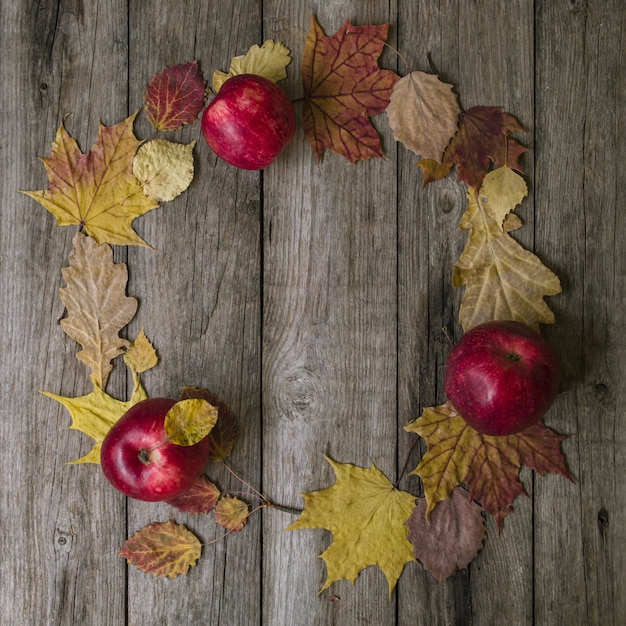 Herbst zusammensetzung. kranz gemacht vom herbstlaub und von den roten äpfeln auf altem hölzernem hintergrund Premium Fotos