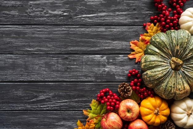 Herbstahornblätter mit kürbis und roten beeren auf altem hölzernem. Premium Fotos