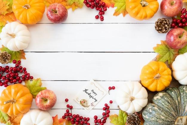Herbstahornblätter mit kürbis und roten beeren auf hölzernem hintergrund. Premium Fotos