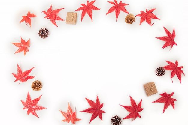 Herbstahornblattzusammensetzung, bunte ahornblätter, kegel, geschenkboxen auf weiß Premium Fotos