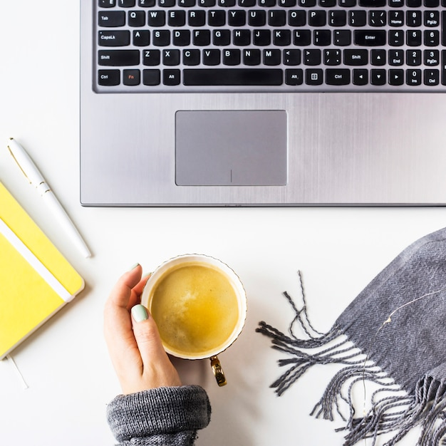 Herbstarbeitsplatz mit laptop, segelflugzeug, stift und kaffeetasse mit den weiblichen händen Premium Fotos