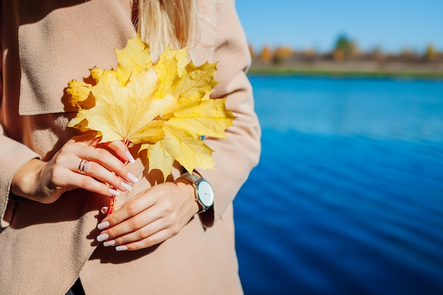 Herbstblätter. junge frau, die durch see geht und gelbe ahornblätter hält Premium Fotos