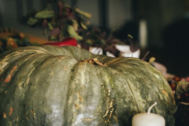 Herbstdekor mit kürbis, kerzen und geschirr Premium Fotos