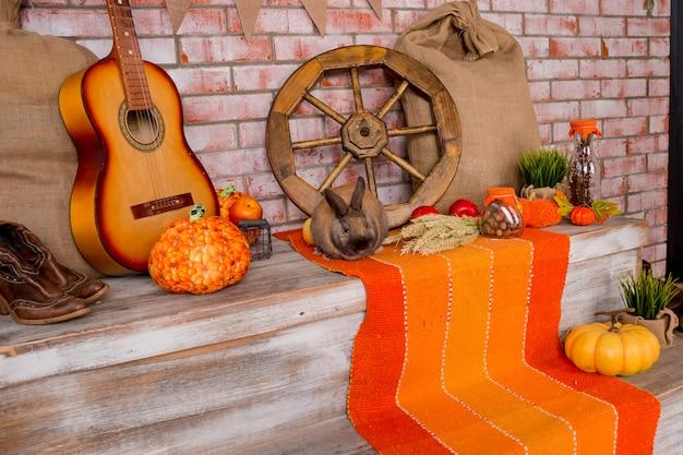 Herbstdekor mit roggen, weizen, mit gelben ahornblättern, kürbisen, roten äpfeln gealtertes holz. saisonale angebote und urlaub postkarte. herbstliche dekoration. Premium Fotos