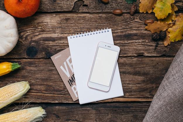 Herbstgemüse: handy mit weißem leerem schirm, kürbisen und mais mit gelb verlässt auf holz Premium Fotos