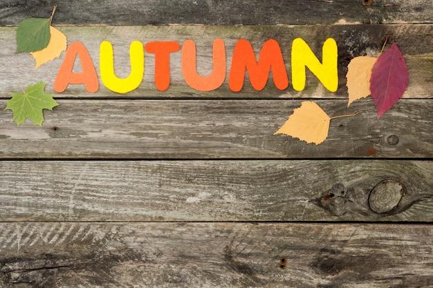 Herbsthintergrund auf altem hölzernem hintergrund, handgemachtes wort herbst aus filz, herbstlaub Premium Fotos