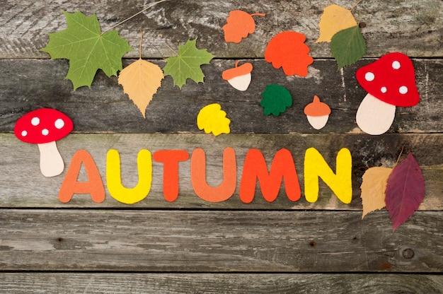 Herbsthintergrund auf altem hölzernen hintergrund, handgemachte blätter, pilze, eicheln und inschrift herbst aus filz Premium Fotos
