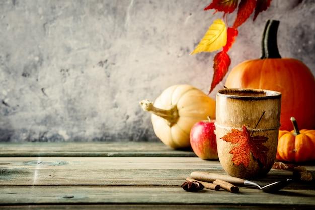 Herbsthintergrund auf hölzernem tabel gegen alte rostzustands-weinlesewand Premium Fotos