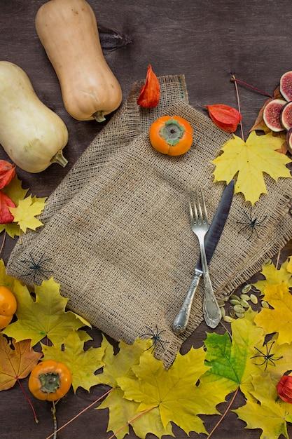 Herbsthintergrund mit gelben ahornblättern, feigen, persimonen und kürbisen. Premium Fotos