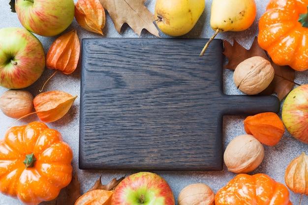 Herbsthintergrund mit gelben blättern, kürbisapfelbirnen und nüssen Premium Fotos