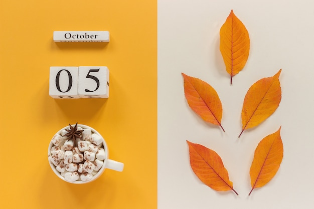 Herbstkalender 5. oktober tasse kakao mit marshmallows und gelbem herbstlaub Premium Fotos