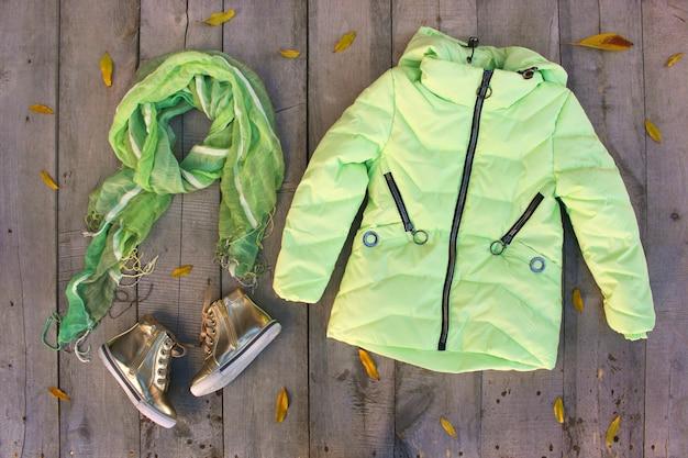 Herbstkleidung der kinder auf bretterboden mit blättern Premium Fotos
